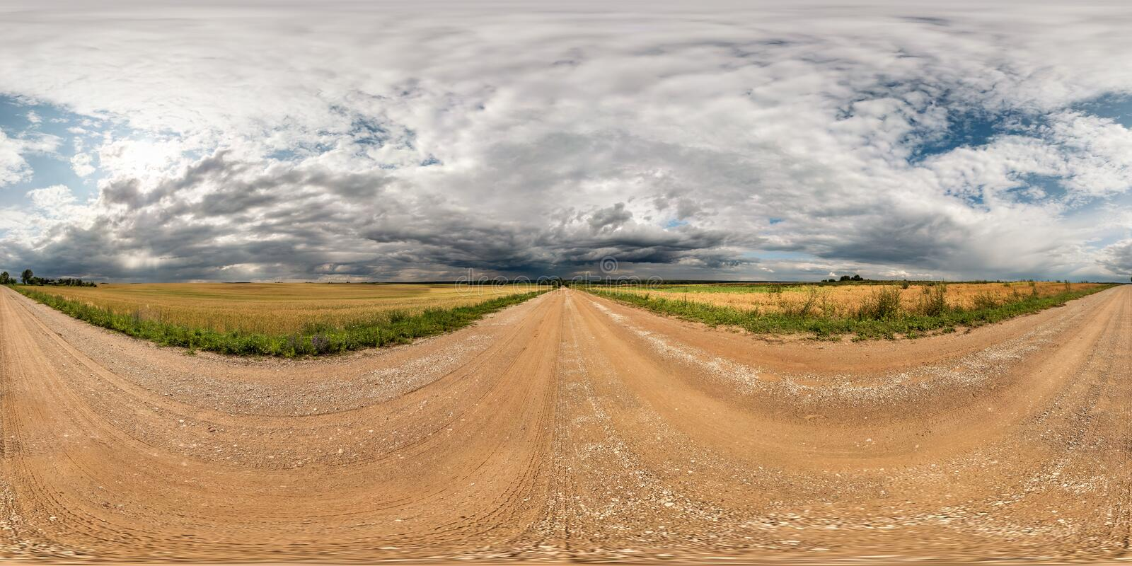 Full seamless spherical hdri panorama 360 degrees angle view on gravel road among fields with awesome clouds before storm in. Equirectangular projection, ready royalty free stock images