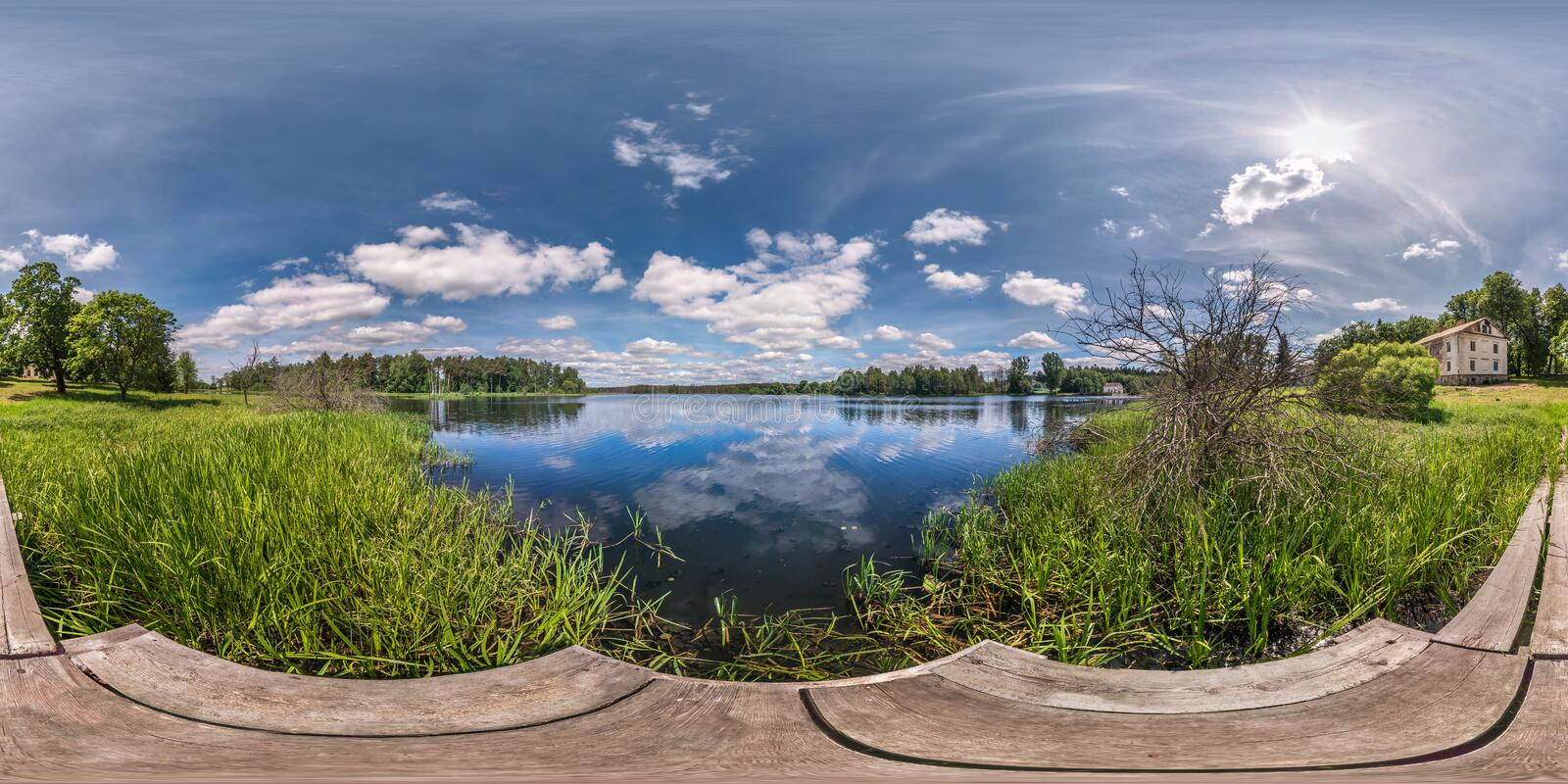 Full seamless spherical hdri panorama 360 degrees  angle view on wooden pier of huge lake or river in sunny summer day and windy. Weather with beautiful clouds stock photo
