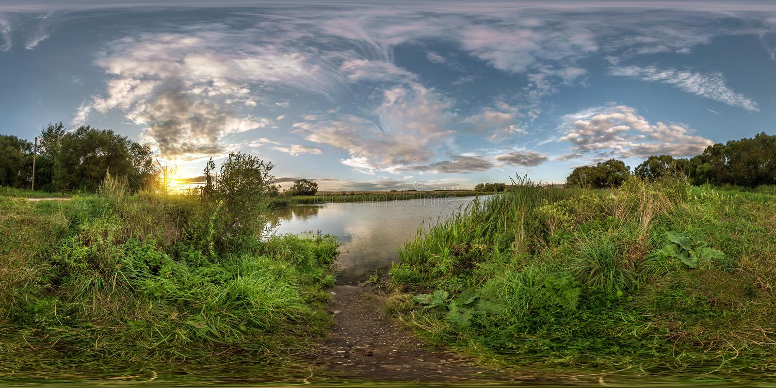 Full seamless spherical panorama 360 by 180 angle view on the shore of small lake in sunny summer evening with awesome clouds in royalty free stock image