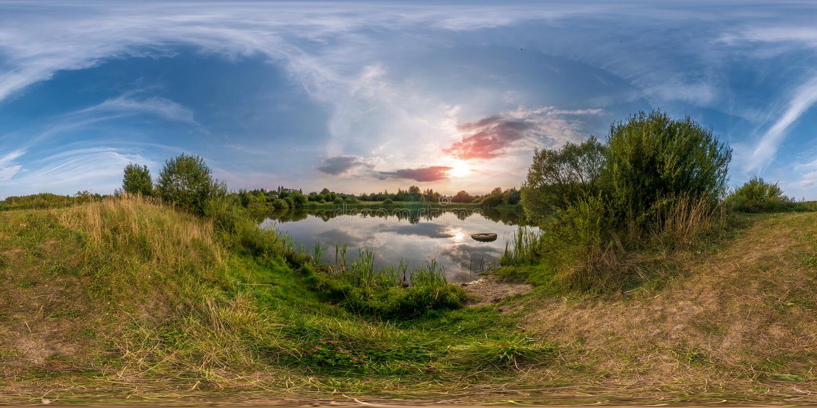 Full seamless spherical panorama 360 by 180 angle view on the shore of small lake in sunny summer evening with awesome clouds in stock image