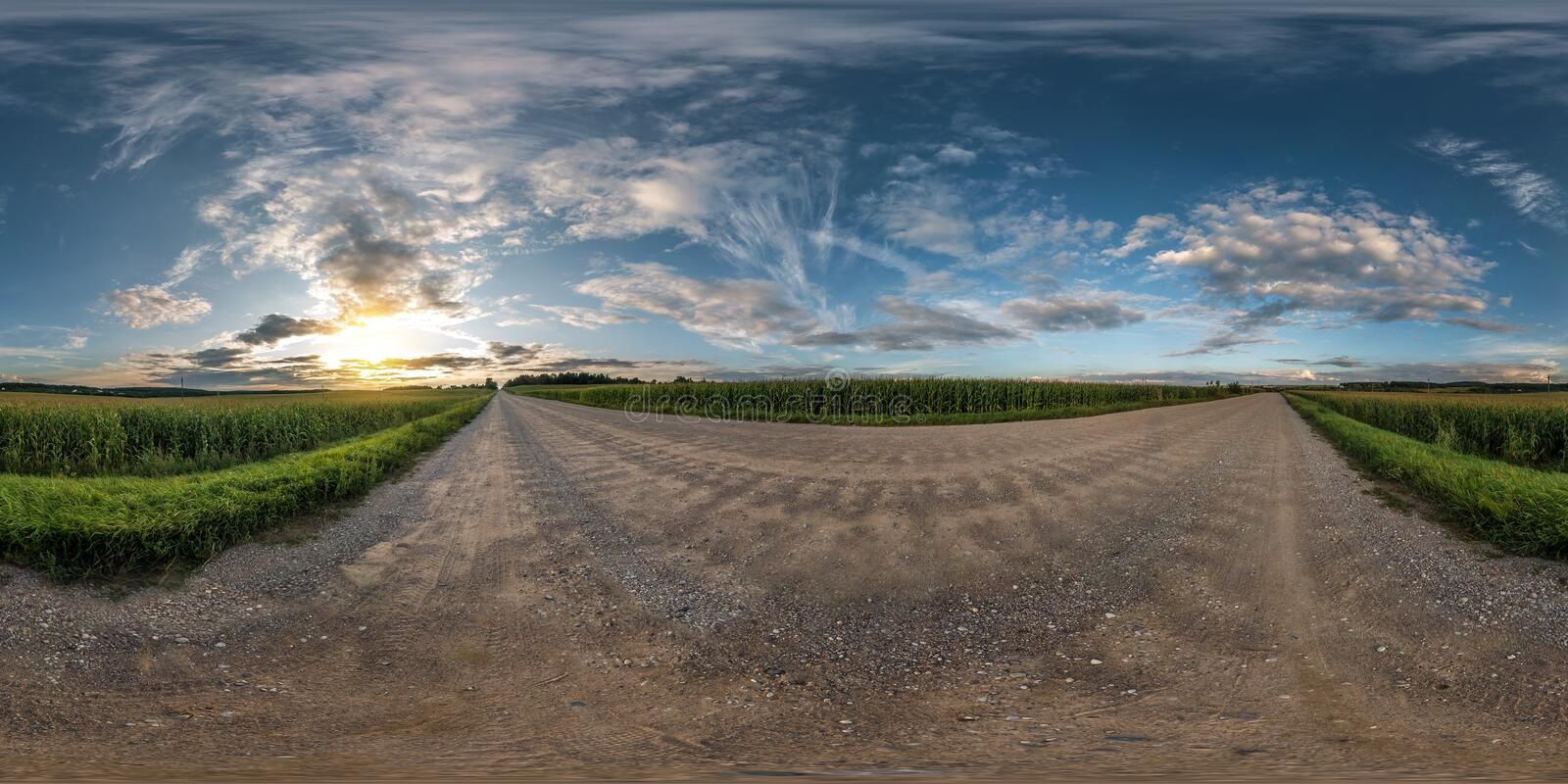 Full seamless spherical panorama 360 degrees angle view on gravel road among fields in summer evening sunset with awesome clouds stock image