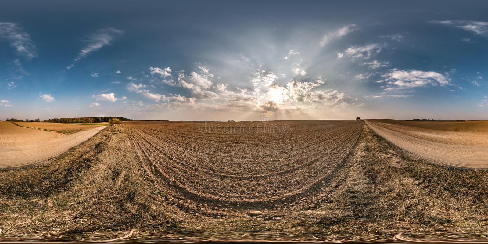 Full seamless spherical panorama 360 degrees angle view near gravel road among meadow fields in spring evening sunset with awesome. Clouds in equirectangular stock images