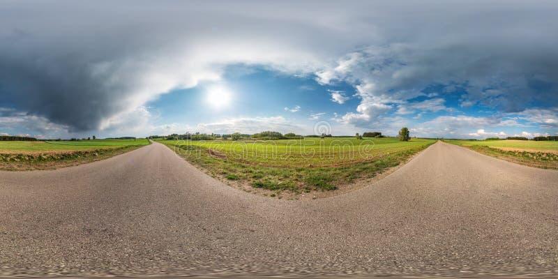 Full sfärisk sömlös panorama 360 grader vinkelsikt på ingen trafikasfaltväg bland gränden och fält med enorma moln in royaltyfri foto