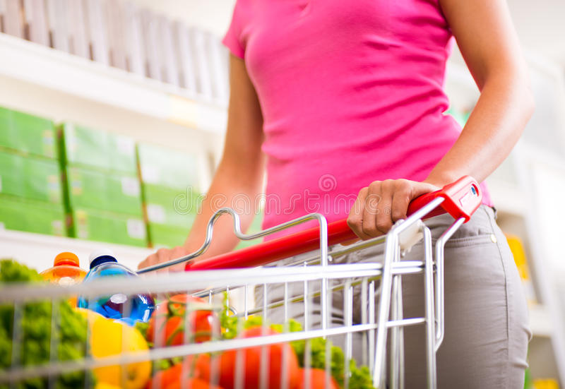 Full shopping cart at supermarket. Full shopping cart at store with fresh vegetables and hands close-up royalty free stock image