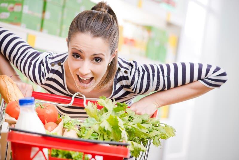 Full shopping cart. Woman gasping and pushing a full shopping cart at supermarket royalty free stock photo
