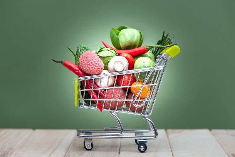 Full shoppingvagn, utrymme för text, baner Vård- bio begrepp för organisk mat, vagn i fulla grönsaker för supermarket arkivfoton