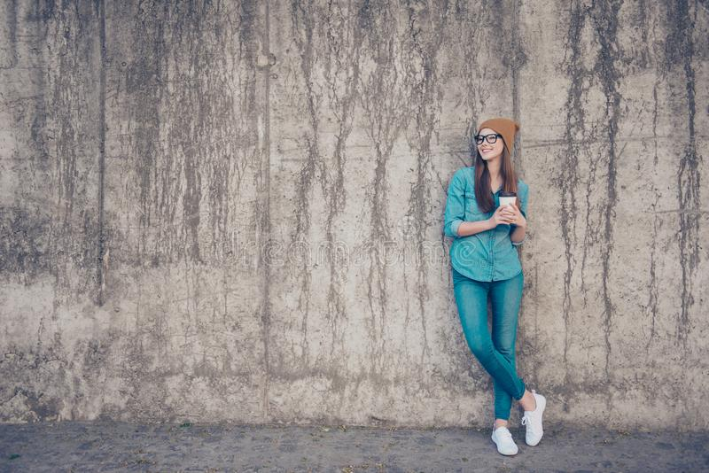 Full size of cheerful young lady, standing near concrete wall outside, smiling, with crossed legs and plastic cup with coffee, in royalty free stock photo