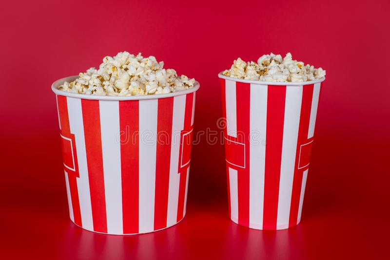 Full size length photo of two middle and bid size containers full of tasty yummy fresh popcorn with place for label text isolated. Vivid background royalty free stock image