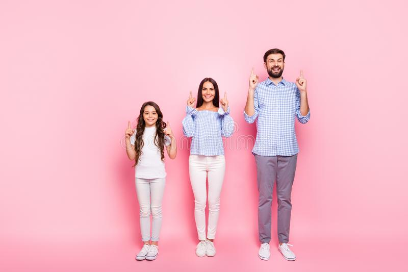 Full size photo of cheerful parents and child with wavy long haircut point at copy space wear plaid checkered shirt stock photography