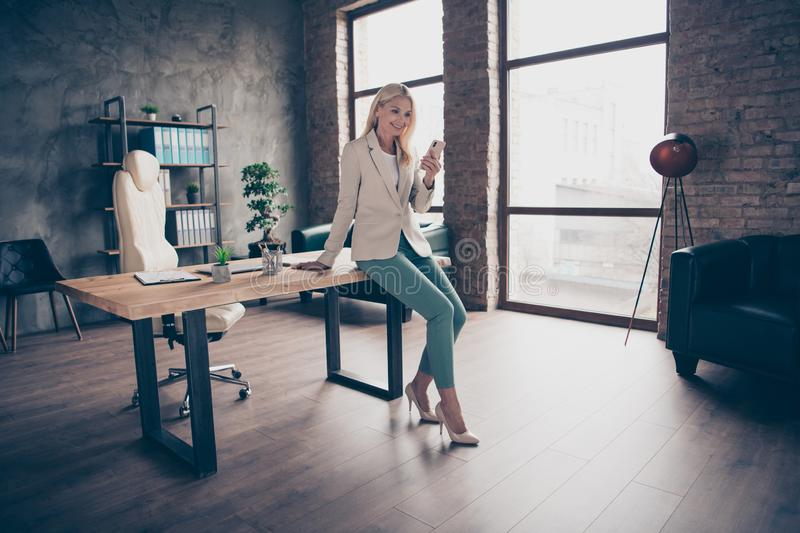 Full size photo of confident focused middle aged leader business woman sit on wooden table in office use her smartphone royalty free stock images