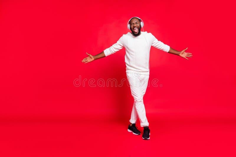 Full size photo of cool dark skin man listening favorite playlist in earflaps enjoy best moment moving with rhythm wear. Full size photo of cool dark skin man stock photos