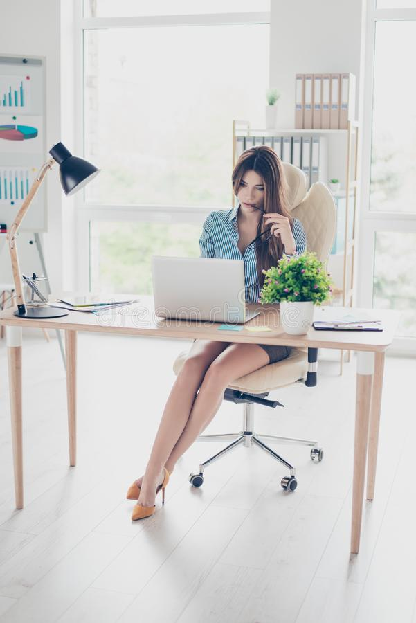 Full size photo of elegant business lady sitting in her office a. Nd browsing info in laptop. She is wearing formal wear and high hills royalty free stock photos