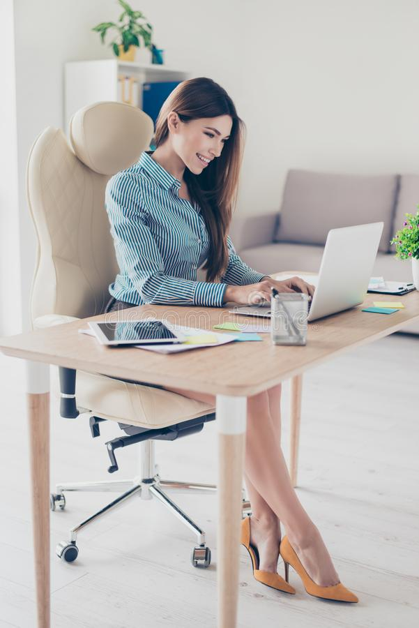 Full size photo of elegant business lady sitting in her office a. Nd typing in laptop. She is wearing formal wear and high hills royalty free stock images