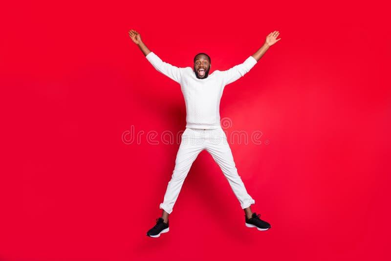 Full size photo of excited dark skin handsome guy jumping high rejoicing having best x-mas party time wear white sweater. Full size photo of excited dark skin stock photo