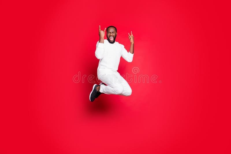 Full size photo of excited dark skin handsome guy jumping high rejoicing at rock concert showing horns hands wear white. Full size photo of excited dark skin stock photography