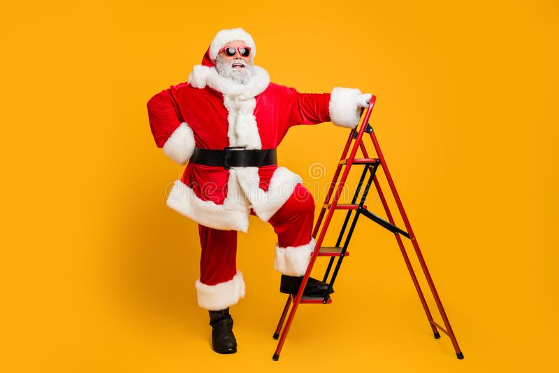 Full size photo of funny funky santa claus in red hat want climb stairs to deliver dream wish gift presents on magic stock images