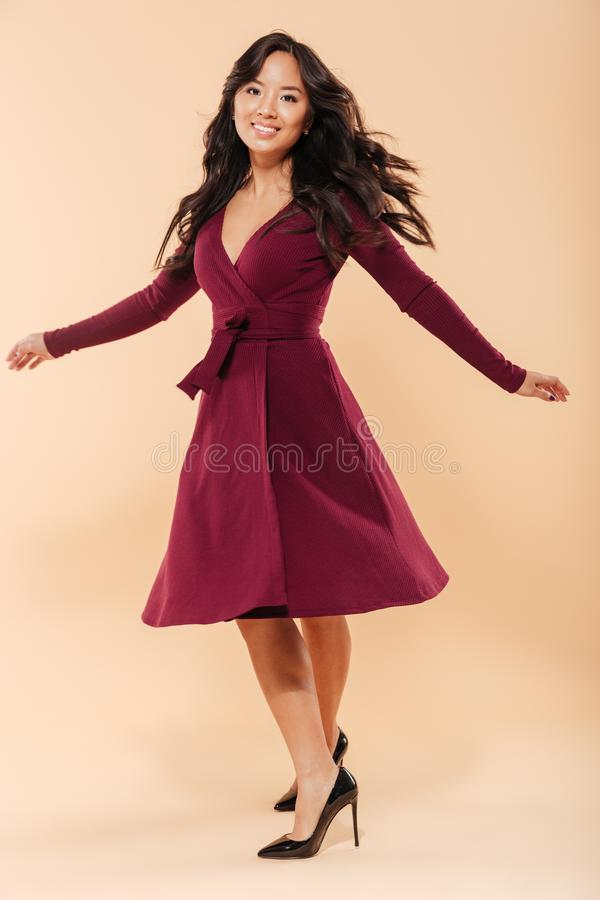 Full size portrait of charming asian female in pretty maroon dress dancing and looking on camera being isolated over beige stock photography