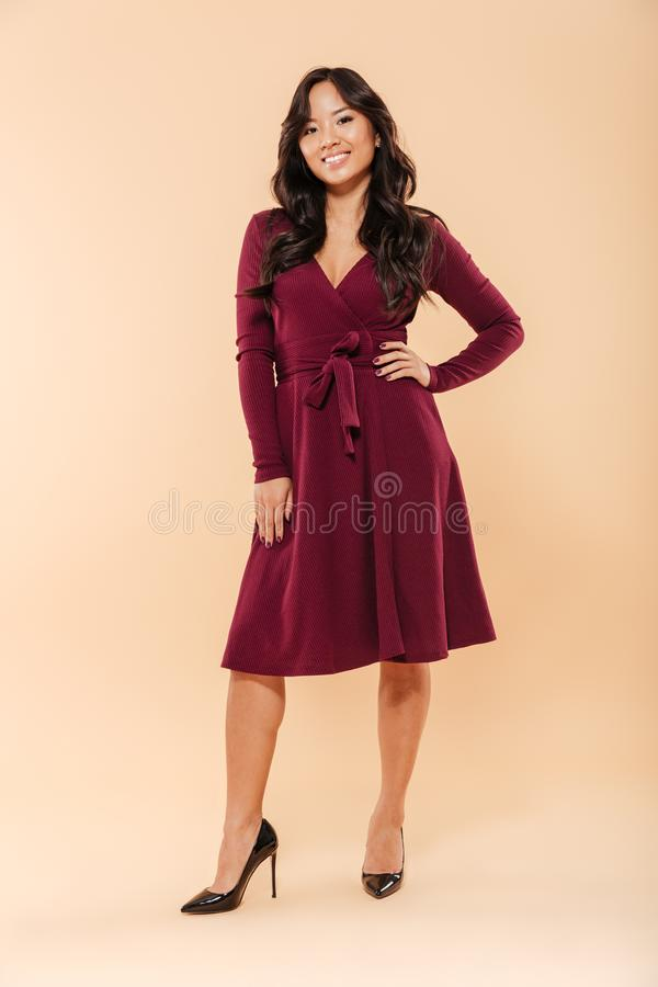 Full size portrait of charming asian female in pretty maroon dress posing over beige background with brilliant smile and hand on. Full size portrait of charming royalty free stock image