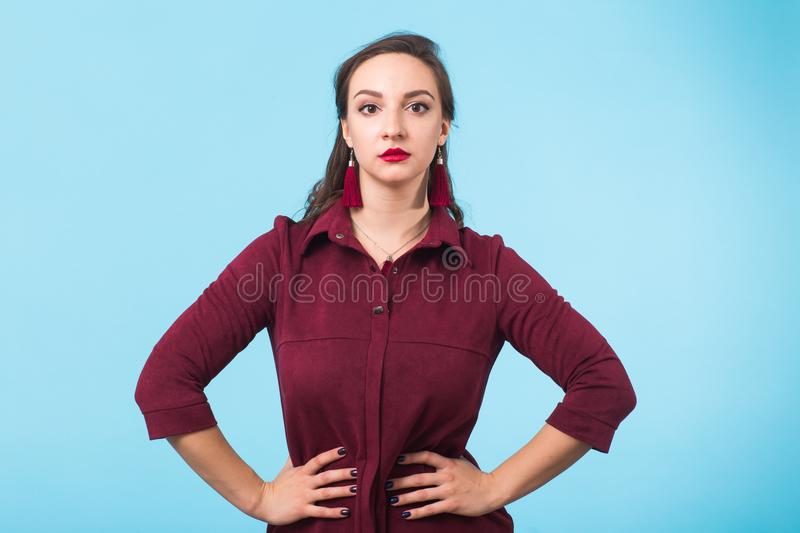 Portrait of serious casual brunette caucasian businesswoman wearing standing on blue background. Looking at camera. royalty free stock photos