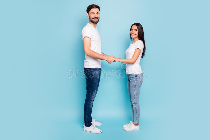 Full size profile side photo of candid satisfied couple hold hand have date free time wear white t-shirt denim jeans stock images