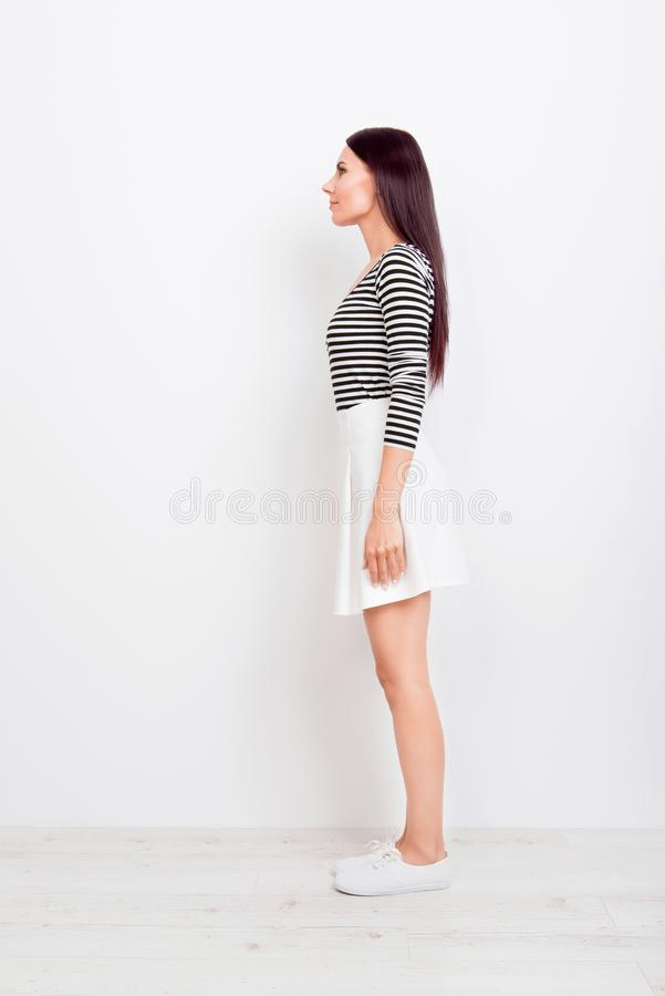 Full size profile view of brunette girl in casual clothes and white shoes on pure white background royalty free stock photo