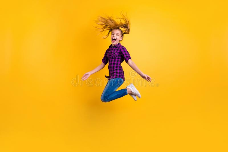 Full size side photo of small pupil jump high hooray holidays wear casual checkered shirt jeans denim isolated yellow royalty free stock image