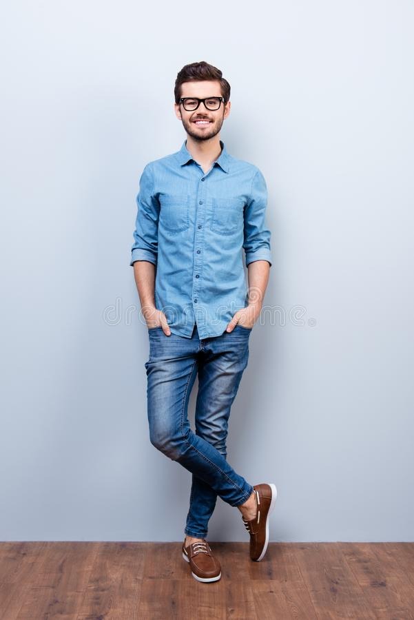 Full size vertical portrait of cheerful brunet young man in casual stylish wear. He looks at camera on lifgt background stock photos