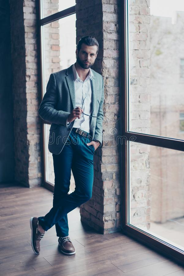 Full size of young business man, who is standing near the window stock images