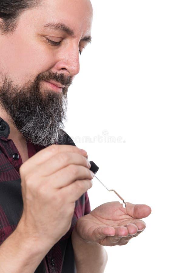 Full skäggig man med skäggolja, skäggomsorgprodukt arkivfoton