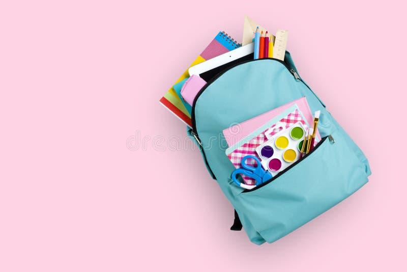 Full skolaryggsäck som isoleras på rosa bakgrund arkivbild