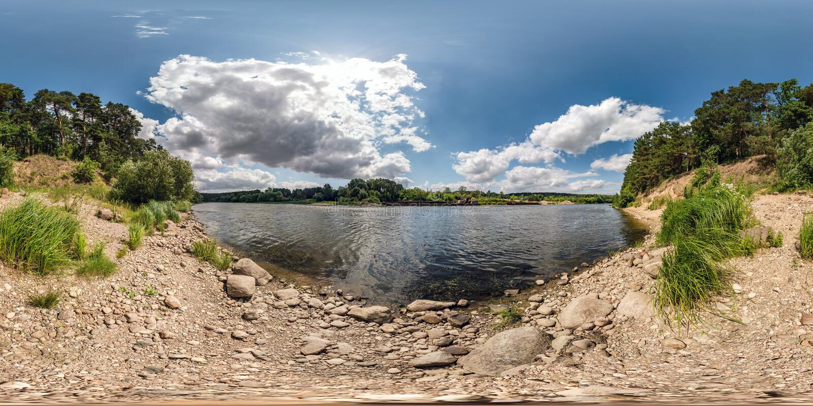 Full spherical seamless hdri panorama 360 degrees angle view on rocky shore of huge river in sunny summer day and windy weather royalty free stock photography