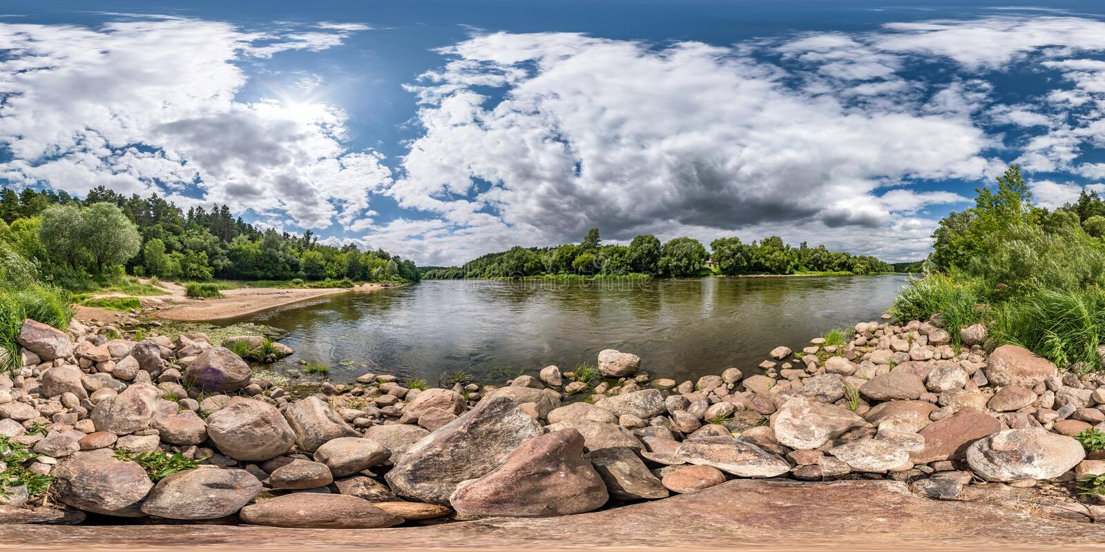 Full spherical seamless hdri panorama 360 degrees angle view on rocky shore of huge river in sunny summer day and windy weather. With beautiful clouds in royalty free stock image