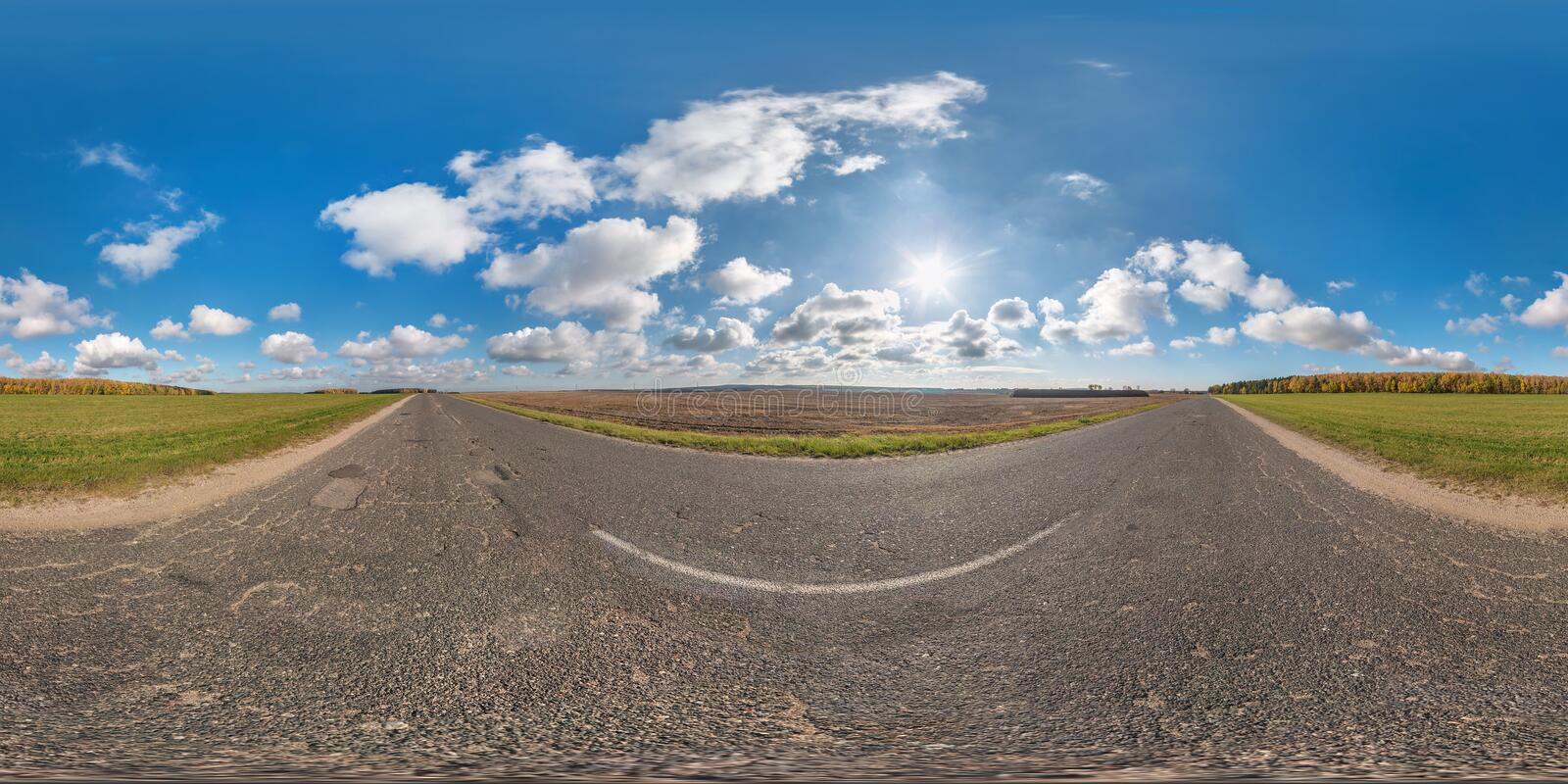 Full spherical seamless panorama 360 degrees angle view on no traffic asphalt road among fields in sunny day with awesome clouds. 360 panorama in royalty free stock image
