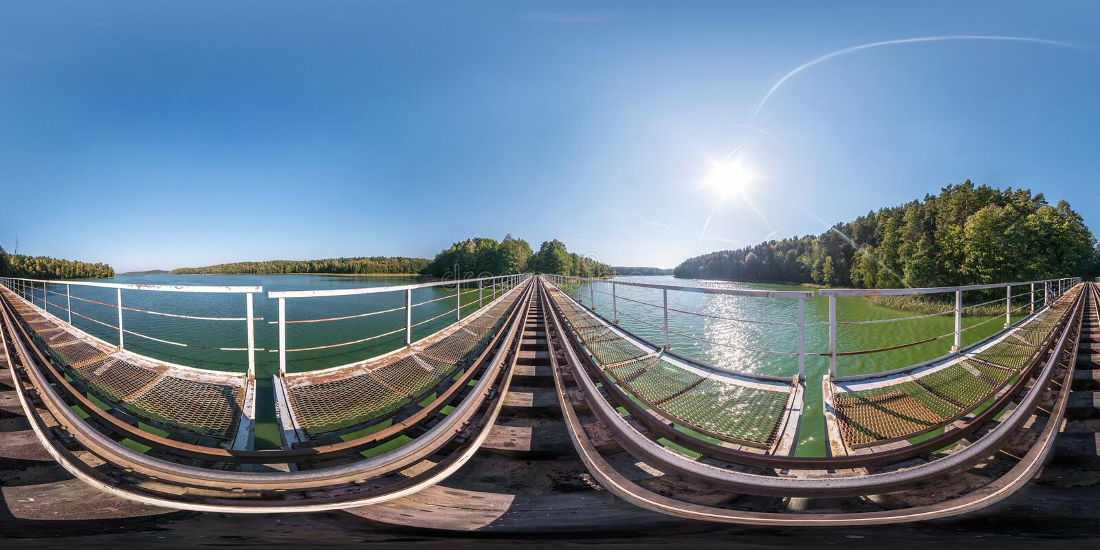 Full spherical seamless panorama 360 degrees angle view on steel frame construction of huge train railway bridge across laked. 360. Panorama in equirectangular royalty free stock images