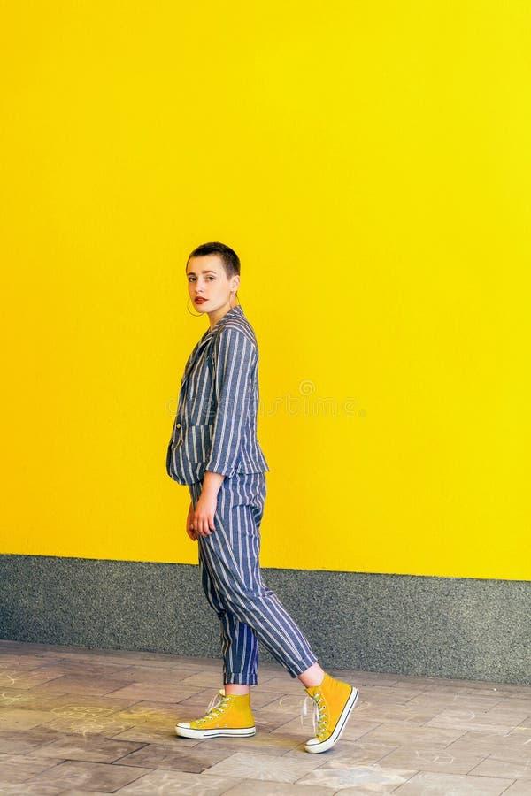 Full stående för längdsidosikt av den allvarliga unga härliga kvinnan för kort hår i gul skjorta och randigt dräktanseende för ti arkivfoton