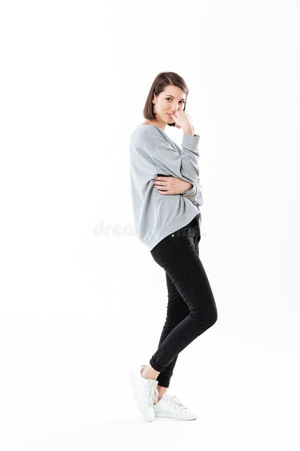 Full stående för längdsidosikt av en eftertänksam ung kvinna arkivfoto