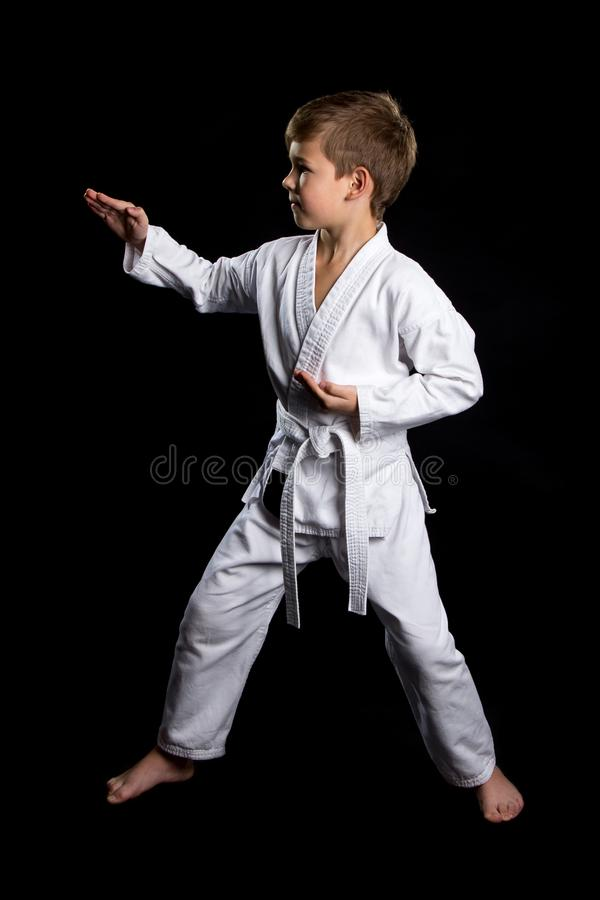 Full stance male fighter in kimono shows pose with open palms. Serious kid in brand new kimono on the black background.  stock photo