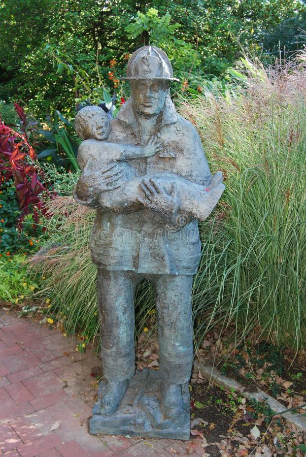 Full Statue of Firefighter saving child royalty free stock photography