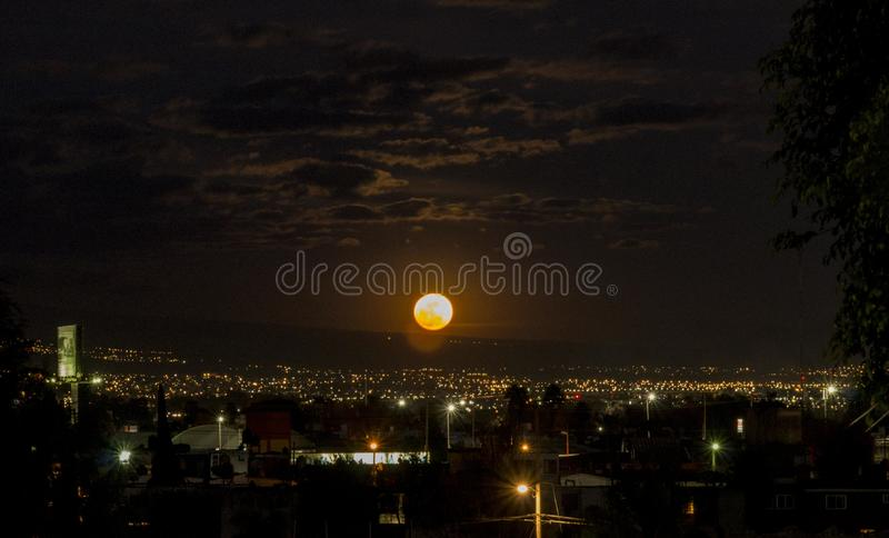 Full super blood moon rising. The blood super moon over the city in the perfect moment with dark clouds royalty free stock photography