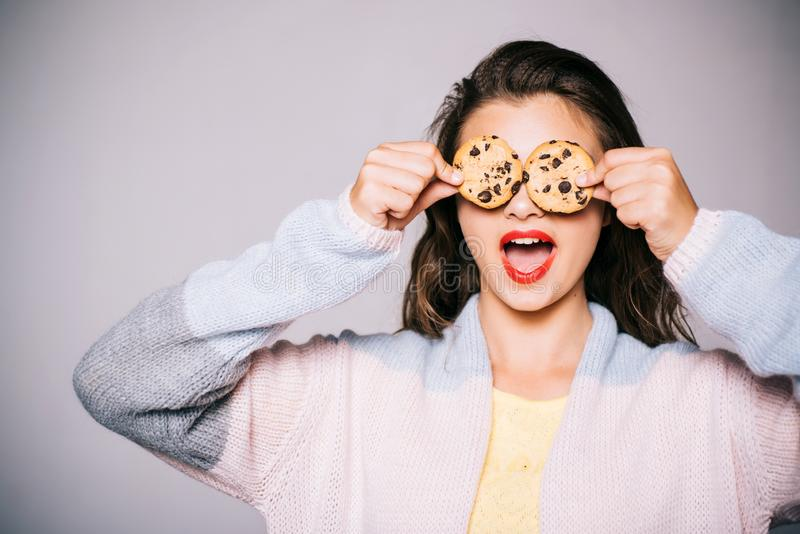 Full of sweet chocolate flavors. Cute girl having fun with cookies. Pretty girl covering eyes with cookies. Bakery style. Chocolate chip cookie recipe. Bakery royalty free stock images