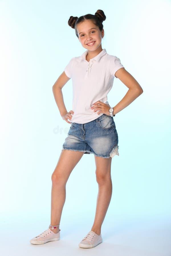 Full tillväxt för lycklig spenslig barnflicka i grov bomullstvillkortslutningar med kala ben fotografering för bildbyråer