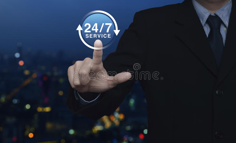 Full time service concept. Businessman pressing button 24 hours service icon over blur colorful night light city tower, Full time service concept royalty free stock photos