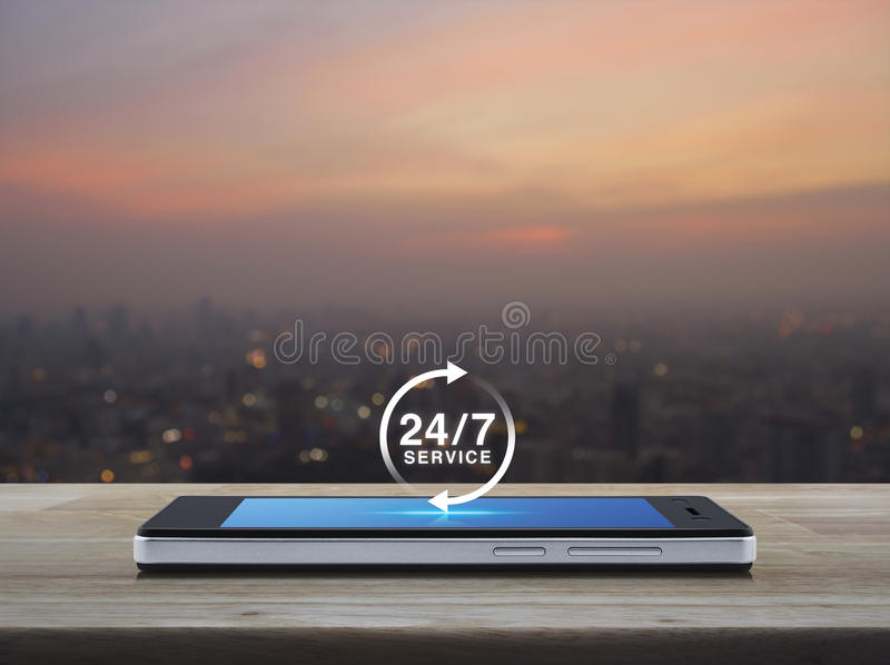 Full time service concept. 24 hours service icon on modern smart phone screen on wooden table over blur of cityscape on warm light sundown, Full time service royalty free stock photo