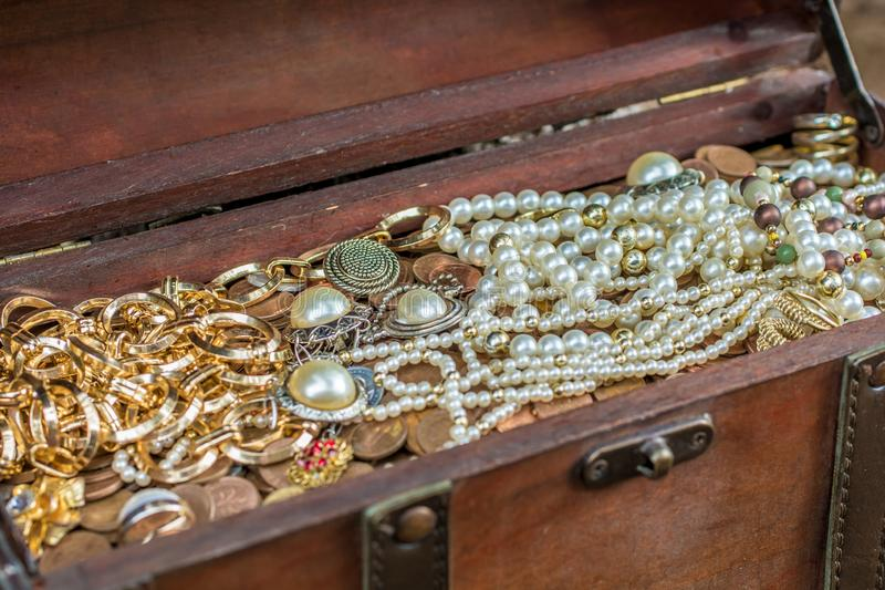 Old treasure chest with precious treasure. A full treasure chest filled with jewelery and coins stock photography