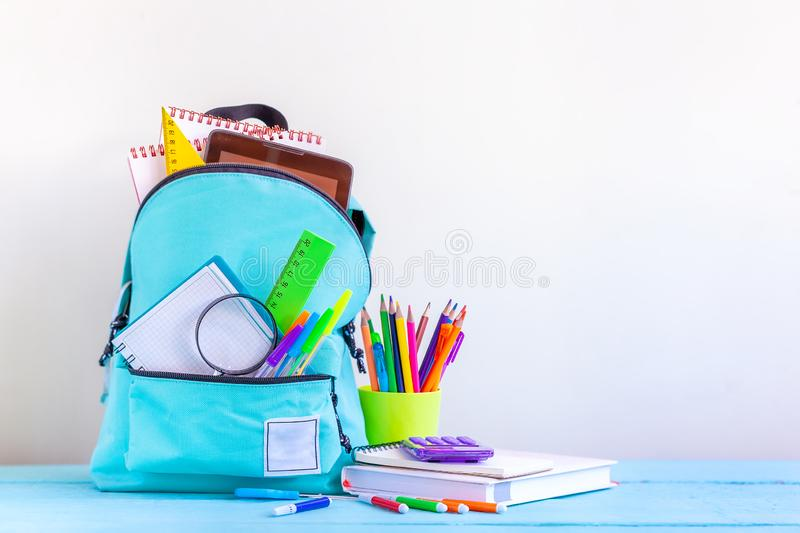 Full turquoise School Backpack with stationery on table stock image
