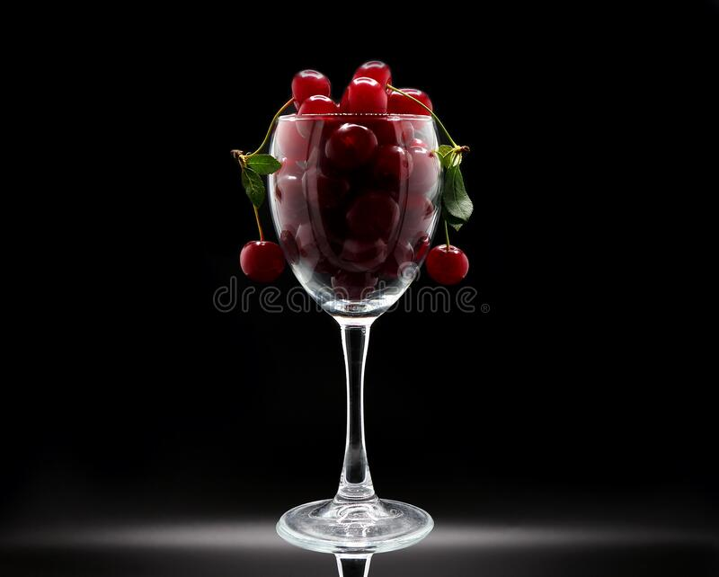 Full wine glass of ripe cherries on a black background. Natural product. royalty free stock photography