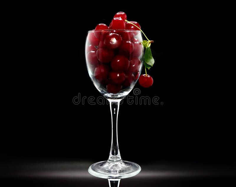 Full wine glass of ripe cherries on a black background. Natural product. stock photography