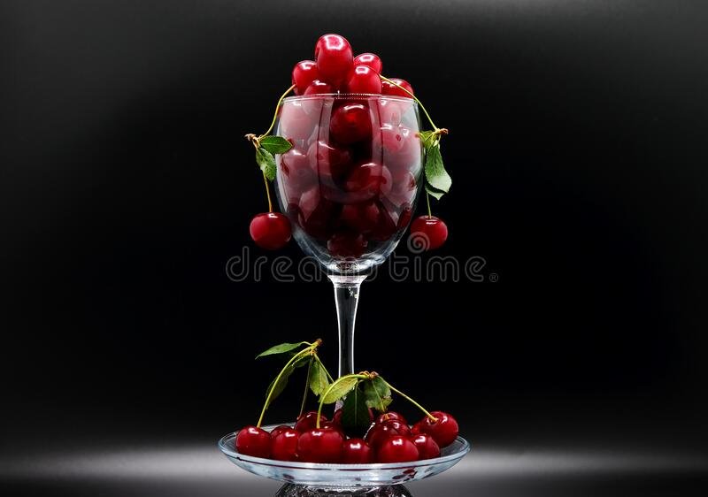 Full wine glass of ripe cherries on a black background. Natural product. stock photo