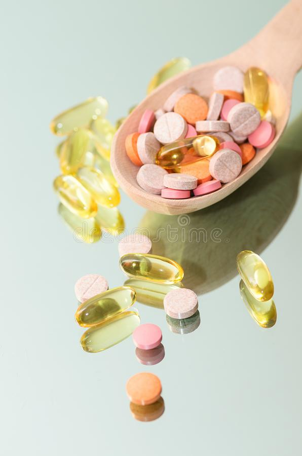 Full wooden spoon of pills, fish oil capsules and other tablets royalty free stock photo