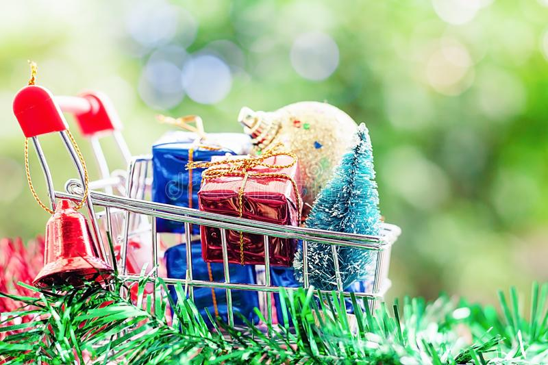 Full of Xmas decorative items in mini shopping cart or trolley a. Gainst blurred natural green background for Christmas and New Year festival concept royalty free stock photos